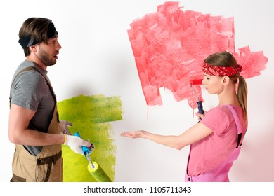 young woman pointing by hand on painted wall to boyfriend while he doing shrug gesture