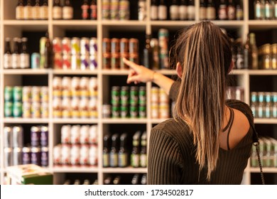 A young woman pointing at canned beers in a liquor shop and choosing some. Beers from trendy small breweries displayed on shelfs. Bokeh background