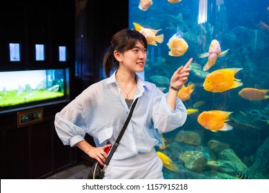 Young woman pointing fish in a fish tank with his finger at underwater world in pattaya,chonburi, thailand.