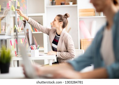 Young woman pointing at working notes on noticeboard while sitting by desk in front of computer monitor