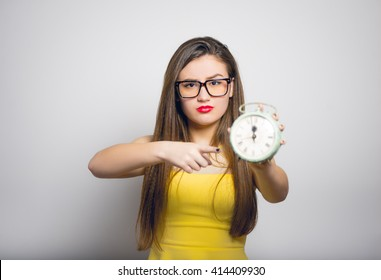young woman points to a retro alarm clock in yellow clothes close-up isolated