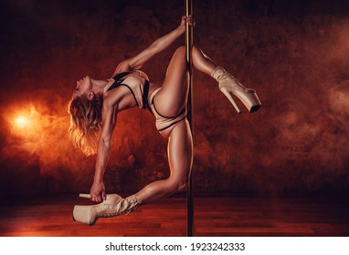 Young woman pole dancing on stone wall with smoke and red lights background