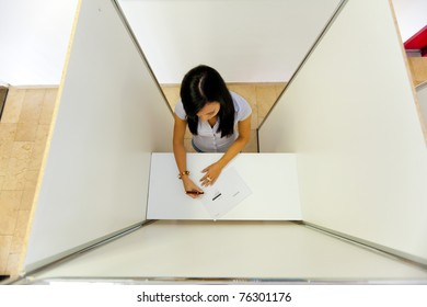 Young woman in a polling booth in the electorate casting their vote