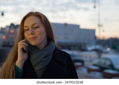 Young woman in polto calls on the phone on the street