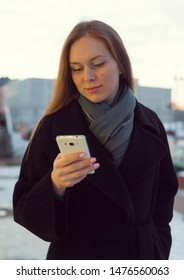 Young woman in polto with a phone on the street