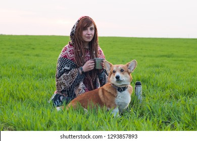 Young woman in poncho with corgi dog relaxing in the spring fields