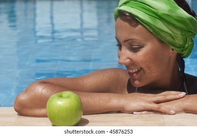 young woman at pool looking to an apple with appetite