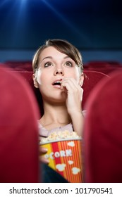 Young woman with popcorn at the cinema