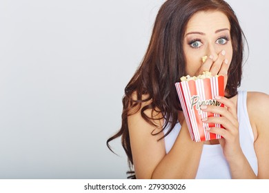 young woman with popcorn in a studio