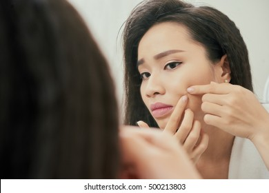 Young woman popping pimple on her cheek