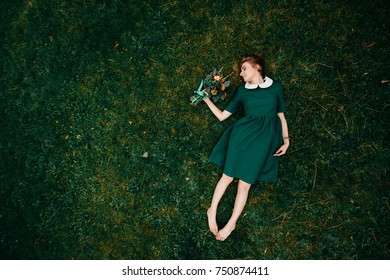 Young woman portrait from above. Beautiful irish cute girl with red hair lying on grass with bouquet of flowers in hand. Minimalism. Fairy tale and fable. Odd strange bizarre female with naked legs.