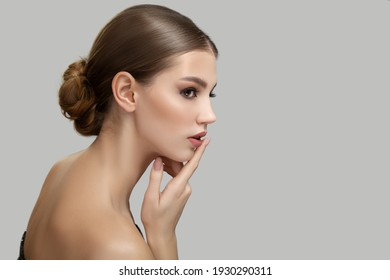 Young woman portrait. Bare shoulders. The hand touches the face. Skin care