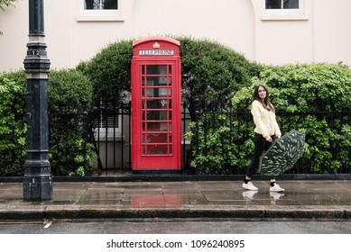 Young woman portrait close to red telephone box in London while raining.