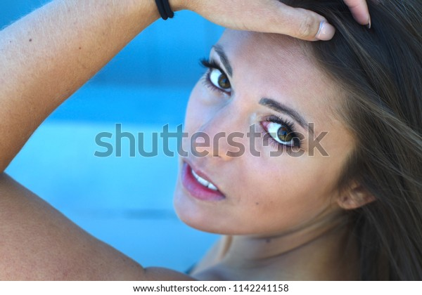 young woman portrait close-up face arm hand in hairs makeup style brunette