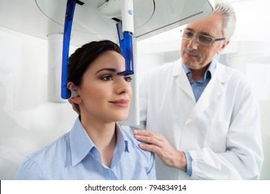 Young woman portrait having panoramic digital X-ray of her teeth with a middle age doctor in the dental office.
