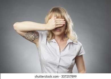 Young woman portrait on grey background, covering her eyes