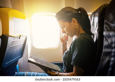 Young woman portrait working with tablet inside airplane. Natural flare from the window. Life style.