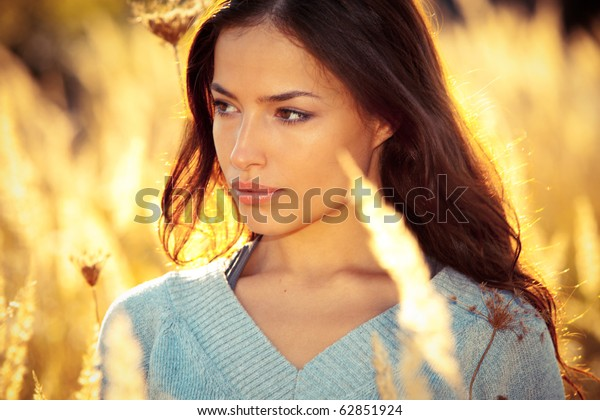young woman portrait in yellow autumn field
