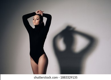 Young woman poses in black bodysuit next to her shadow against of grey background.