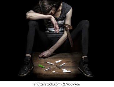 Young woman poses as drug addict, concept photo against black wall. Strong contrast and texture to strengthen message.