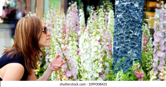 A young woman poses in front of a flower display at a local Chelsea shop in London, UK as part of a popular flower show every May