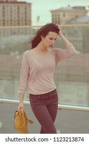 A young woman poses near a glass wall in the city. Street dress style. She wears Burgundy jeans, a pink shirt. Looking down