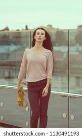 A young woman poses near a glass wall in the city. Street dress style. She wears Burgundy jeans, a pink shirt and a yellow bag in her right hand.