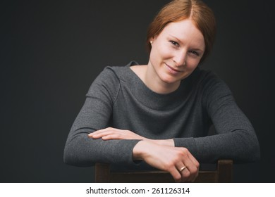 A young woman poses of a studio portrait on an old wooden chair before a plain dark background.