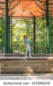 Young woman posing in the beautiful green garden pavilion. Mestsky or City park of Kosice, Slovakia (Slovensko), vertical image. People, travel and summer holidays concept - Shutterstock ID 1472005670