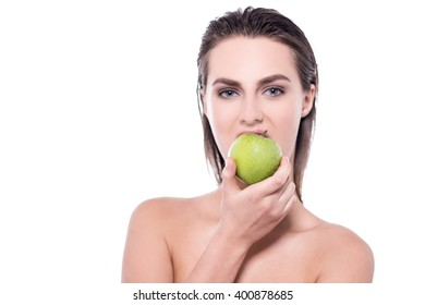 Young woman posing to camera with an apple in her hand