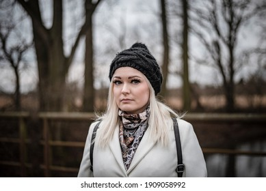 Young woman posing during a winter walk while social distancing, wearing a backpack and black and white outfit