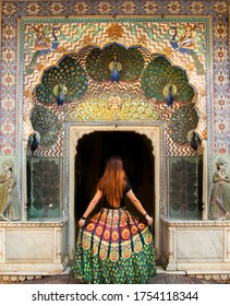 Young woman is posing in front of the peacock city palace door in Jaipur