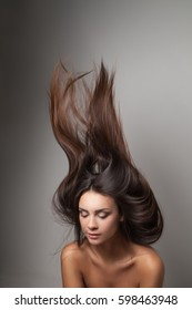 Young woman posing with her long hair thrown up. Vertical studio shot.