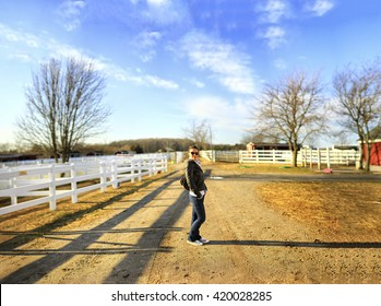 Young woman posing in the middle of a farm. Large jpeg file. Panorama. Brenizer method.
