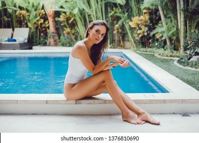 Young woman posing near swimming pool