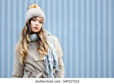 Young woman posing outdoor in winter. Fashion portrait of pretty girl in cold spring weather.