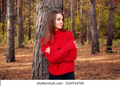 Young woman posing in the red sweater on the autumn park background.