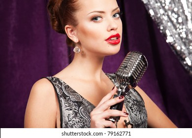 A young woman posing with retro microphone
