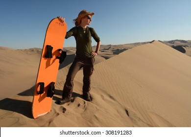Young woman posing with the sandboard, Oasis of Huacachina, Atacama Desert, Peru