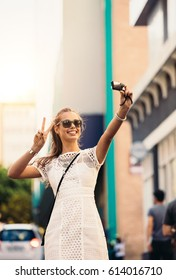 Young woman posing for a selfie in a street flashing victory sign. Vlogger recording content for her travel vlog.