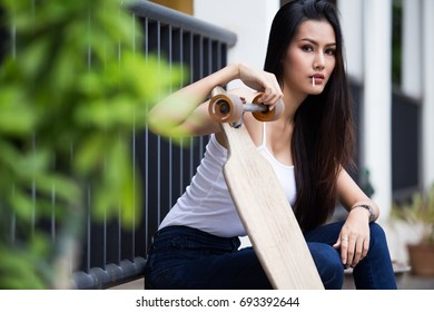 Young woman is posing with skateboard in the city. Female outdoor with long board.
