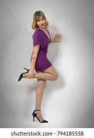 young woman posing standing against a white background, wearing a purple mini dress