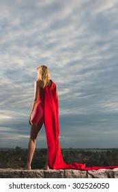 Young woman posing as superhero over the city
