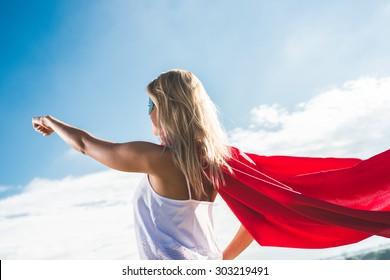 Young woman posing as superhero over blue sky