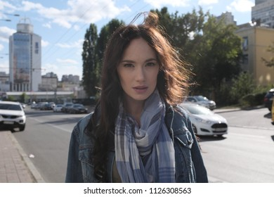 Young woman posing while walking around the city in windy weather. She wears a blue jeans jacket with a scarf. The wind plays with her beautiful long brown hair