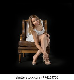 young woman posing in white dress, touching her legs