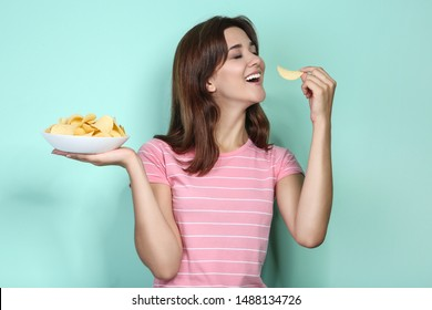 Young woman with potato chips in plate on mint background