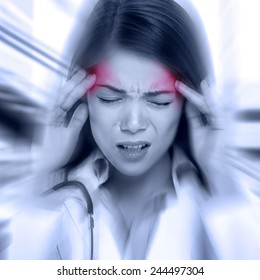 Young woman with a pounding headache or migraine standing clutching her temples with an expression of pain, monochrome image with selective red color to temples and blur effect around her face