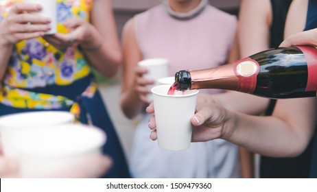 Young woman pouring champagne into glass, close-up outdoors. Young people celebrating with champagne at party outdoors. Concept of hen-party or corporate