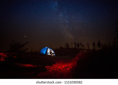 Young woman pouring coffee from thermos in night camp on mountain trail. Szczyrk, Beskidy Mountains, Poland